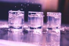 Tres vidrios de la vodka con salpican Fotografía de archivo