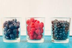 Tres vidrios de las bayas del verano - frambuesas, arándanos fotos de archivo libres de regalías