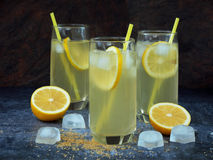 Tres vidrios de limonada hecha en casa fría con las rebanadas del limón, los cubos de hielo, el azúcar marrón y la paja Imagen de archivo