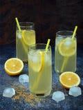 Tres vidrios de limonada hecha en casa fría con las rebanadas del limón, los cubos de hielo, el azúcar marrón y la paja en fondo  Imagen de archivo