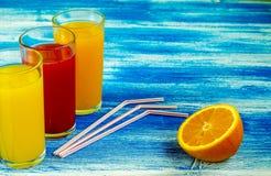 Tres vidrios de refrescos están en un fondo azul Rebanadas de una naranja Bebidas del verano y forma de vida sana imágenes de archivo libres de regalías