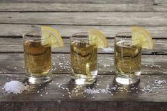 Tres vidrios de tequila con el limón y la sal Foto de archivo