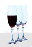 Tres vidrios de vino, uno con el vino Imagen de archivo