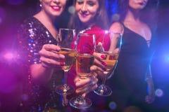 Tres vidrios del tintineo de las mujeres con champán imagen de archivo libre de regalías