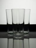 Tres vidrios vacíos en un fondo blanco y negro con reflecti Fotos de archivo