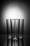 Tres vidrios vacíos en un fondo blanco y negro con reflecti Fotografía de archivo libre de regalías