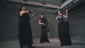 Tres violinistas de las mujeres en los vestidos negros hermosos que tocan los instrumentos en un cuarto concreto gris almacen de video