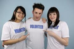 Tres voluntarios felices de los jóvenes Imágenes de archivo libres de regalías