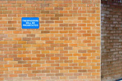 Trespassers will be prosecuted. Sign on new brick wall New. Copyspace Stock Images