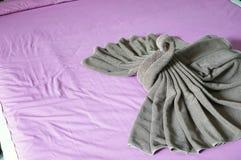 Tresse de serviette de Brown comme cygne sur le lit rose Photo libre de droits