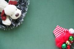 Tresse du ` s de nouvelle année, boules, un chapeau rouge, un chien de jouet sur un fond vert Endroit pour l'inscription Photos libres de droits