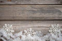 Tresse et flocons de neige blancs sur le conseil en bois Images libres de droits