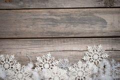 Tresse et flocons de neige blancs sur le conseil en bois Photographie stock