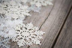 Tresse et flocons de neige blancs sur le conseil en bois Images stock