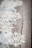 Tresse et flocons de neige blancs sur le conseil en bois Photo libre de droits
