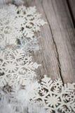 Tresse et flocons de neige blancs sur le conseil en bois Image stock
