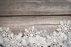 Tresse et flocons de neige blancs sur le conseil en bois Image libre de droits