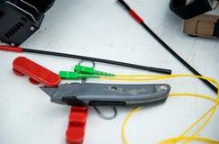 Tresse optique de fibre avec le tube de coupeur et de rétrécissement sur en bois blanc Photos stock