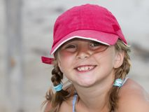 Tressed smiling girl wearing baseball cap Royalty Free Stock Photo