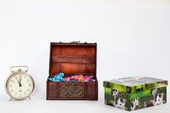 Tresure ask mycket av färgrika konfektar med en klocka som visar laen Royaltyfri Bild