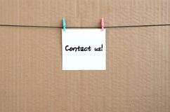 Treten Sie mit uns in Verbindung! Anmerkung wird auf einen weißen Aufkleber geschrieben, der mit a hängt stockbilder