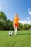 Tretender Fußball des glücklichen Jungen mit seinem Bein Stockbilder