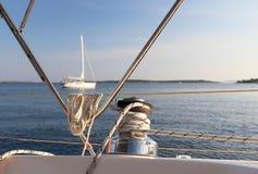 Treuil squelettique ? bord d'un yacht de navigation de croisi?re La vue de l'habitacle sur le navire adjacent à l'ancre Matin tra image libre de droits