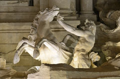 Trevi Fountain triton and hippocamp at night. Beautiful Trevi Fountain detail with marble triton statue Stock Photo