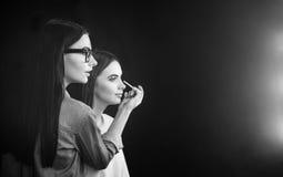 Trevlig allvarlig makeupkonstnär som arbetar med en modell Royaltyfria Bilder