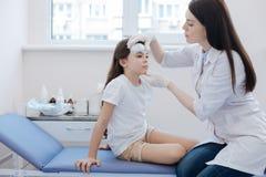 Trevlig angenäm doktor som rymmer flickahuvudet royaltyfri foto