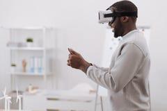 Trevlig angenäm man som använder virtuell verklighetexponeringsglas Royaltyfri Foto