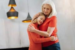 Trevlig att bry sig kvinna som kramar hennes sondotter Arkivbild