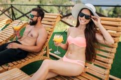 Trevlig bild av flicka- och grabbsammanträde på sunbeds Hon ser på kamera och ler Flickan trycker på hennes solglasögon Hon poser royaltyfria bilder
