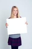 Trevlig blond flicka som visar ett vitt tecken Royaltyfri Foto