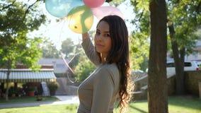 Trevlig brunett med ballonger i handen som går på en bakgrund av solljus- och gräsplanträd lager videofilmer
