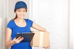 Trevlig deliverywoman som står den near dörren Fotografering för Bildbyråer