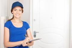 Trevlig deliverywoman som står den near dörren Royaltyfri Bild