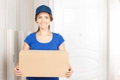 Trevlig deliverywoman som står den near dörren Arkivfoton
