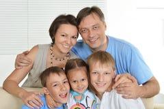 Trevlig familj av fem som sitter arkivfoton