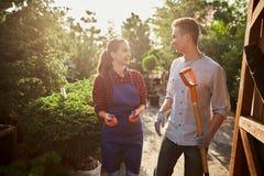 Trevlig flicka för trädgårdsmästare i förklädet och grabben med en skyffel som går på trädgårdbanan i den underbara trädgården på royaltyfri fotografi