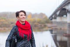 Trevlig flicka i den utomhus- röda halsduken Arkivfoto