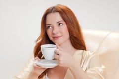 Trevlig flicka i kappa för beigahemdressing med en kopp kaffe Arkivbild