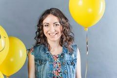 Trevlig flicka med gula ballonger Fotografering för Bildbyråer
