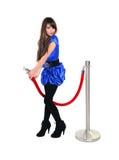 Trevlig flicka som poserar nära barriär för rött rep Fotografering för Bildbyråer