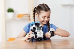 Trevlig flicka som spelar med roboten Royaltyfri Foto