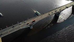 Trevlig flyg- längd i fot räknat av en bro med bilar och bussar med skeppet som går ner floden under bron arkivfilmer