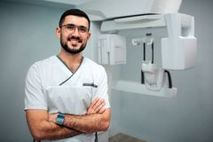 Trevlig gladlynt tandläkareställning i röntgenstrålerum och att posera på kamera Han ler Röntgenapparat bakom royaltyfri bild