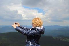 Trevlig kvinna som förbi fotograferar telefonen en enorm bergsikt Arkivfoto