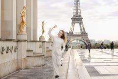 Trevlig kvinna som går på Trocadero den fyrkantiga near förgyllda statyer och Eiffeltorn Arkivfoton