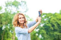 Trevlig kvinna som tar bilder med smartphonen Royaltyfria Foton